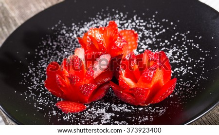 Three roses from ripe strawberry on a black plate, are sugared. Close up, horizontal shot, small depth of sharpness - stock photo