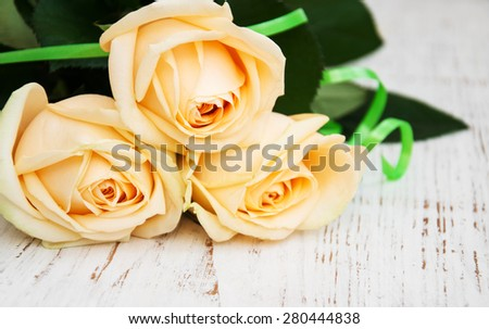 Three Roses on a old wooden table