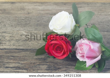 Three roses:red, white, pink lie on a wooden - stock photo