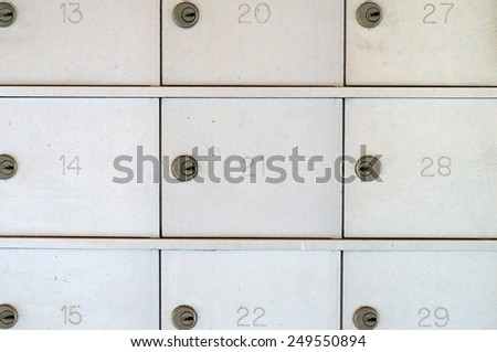 three rows of locked numbered silver metal mailboxes fill the frame. - stock photo