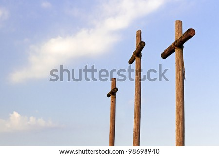 Three rugged, wooden crosses stand against a blue, cloudy sky with excellent text space.
