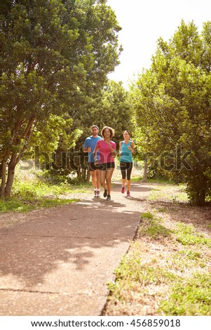 Three runners on a paved jogging trail in daylight surrounded by trees and bushes in the late morning wearing t-shirts and black pants