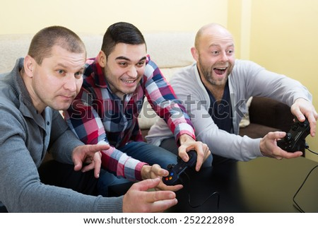 Three russian shouting friends playing video games at house party - stock photo