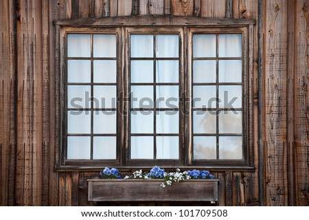 Three rustic windows with a window flower box - stock photo