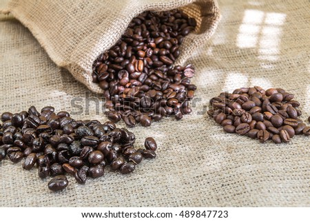 three samples pure Arabica coffee beans of various origins and different roasting on burlap