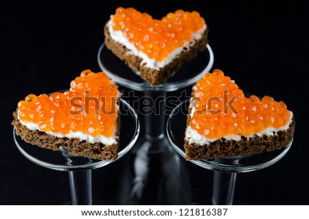 three sandwich with red caviar in the form of a heart on glass stand base