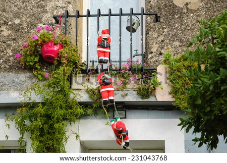 Three Santa Claus figures climbing up a wall into a window. Traditional Christmas decoration.  - stock photo