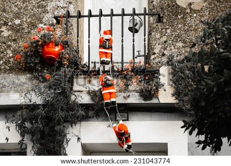 Three Santa Claus figures climbing up a wall into a window. Traditional Christmas decoration. Aged photo. - stock photo