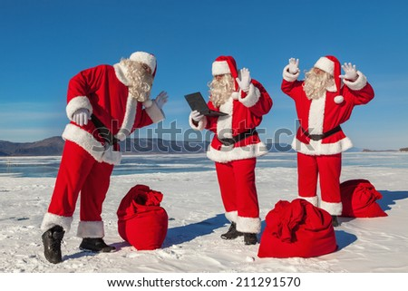Three Santa Claus talking to someone on the Internet in winter, multiexposition, shooting was conducted in a sunny day on lake Baikal - stock photo