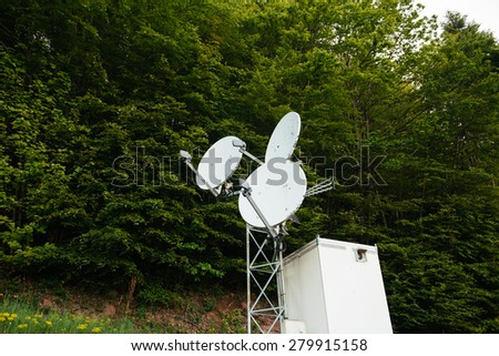 Three satellite dish on a communication tower in the middle of a green forest - stock photo