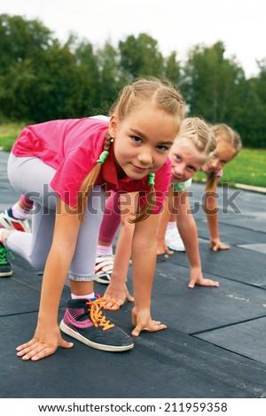 Three schoolgirls are at the start on the treadmill - stock photo