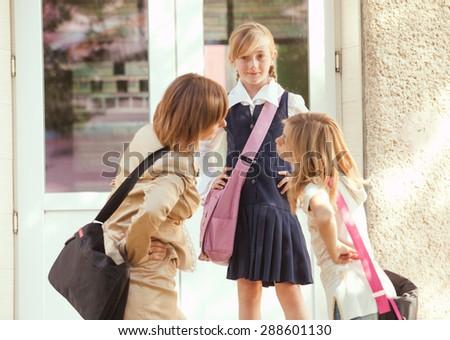 Three schoolgirls outdoors near the door of school building - stock photo