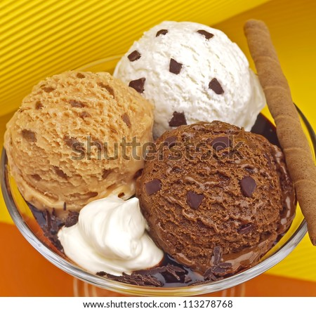 Three scoops of caramel chocolate and vanilla  ice cream - stock photo