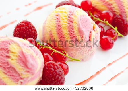 Three scoops of raspberry ice cream with fresh raspberries and red currants - stock photo