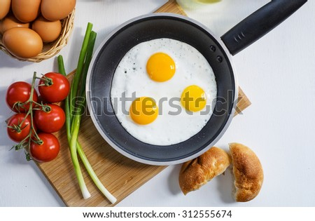 Three scrambled eggs on a frying pan with green onion, bread, a basket eggs, tomatoes, on a white table.