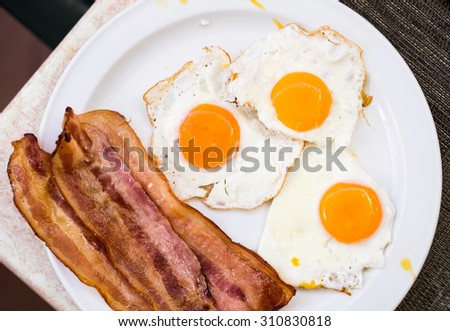 Three scrambled eggs with bacon on a white plate on a table.