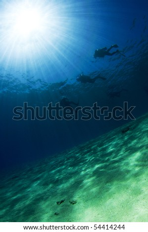 three scuba divers silouetted - stock photo
