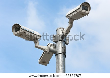 Three security cameras against blue sky