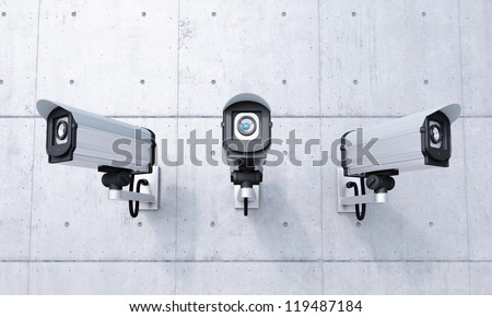 Three Security cameras frontal view on concrete wall - stock photo