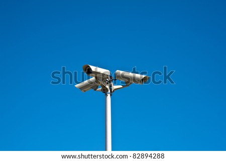 Three security cameras isolated on a blue sky - stock photo