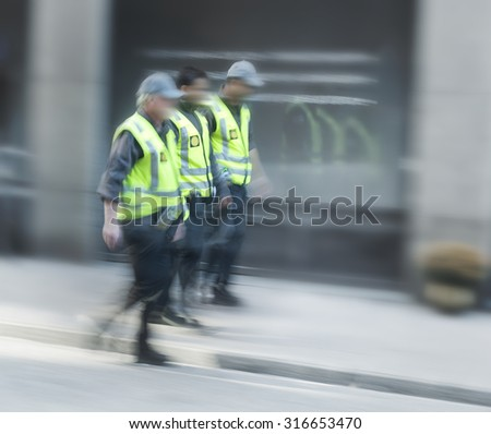 Three security guards in a row walking down the street - stock photo