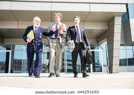 Three senior businessmen walking outdoors - Managers talking about business - stock photo