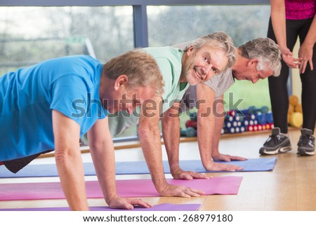 Three senior men doing press ups at the gym - stock photo