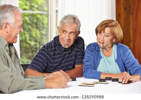 Three senior people playing domino together in a retirement home - stock photo