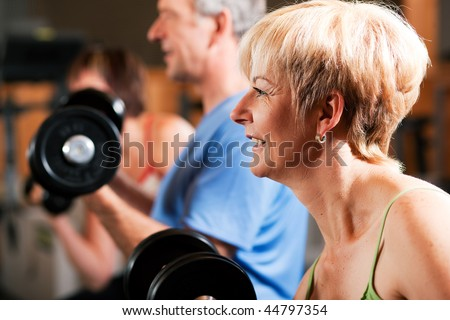 Three senior people - two women and one man - in the gym lifting dumbbells, exercising - stock photo