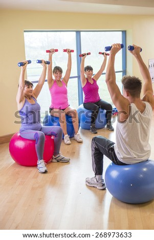 Three senior women doing weights using equipment with the guidance of a fitness instructor