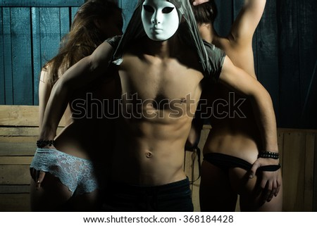 Three sensual young adult people of handsome muscular man with hidden face by mask with attractive naked girls with slim body  in erotic panties in sexual relations indoor on wood backdrop, horizontal - stock photo