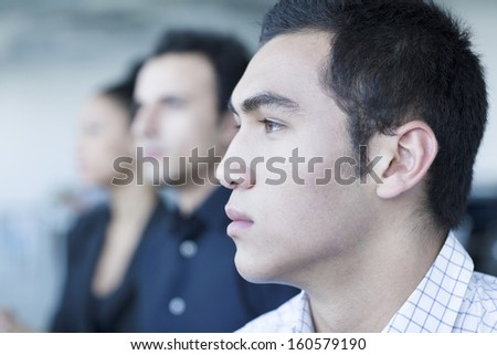 Three serious business people sitting in business meeting - stock photo