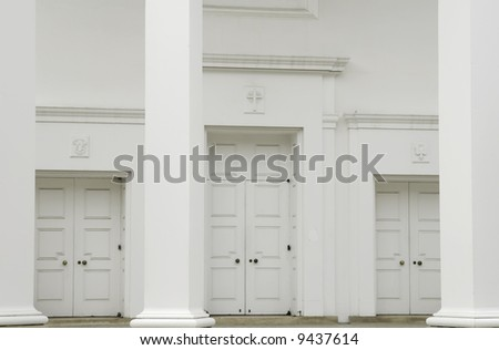 Three sets of tall doors at front of Protestant church - stock photo
