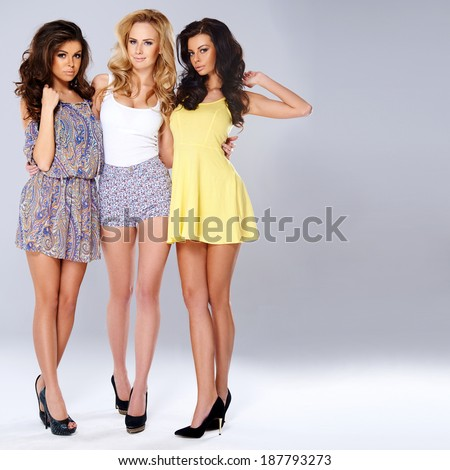 Three sexy chic young women in summer fashion standing arm in arm showing off their long shapely slender legs, studio background