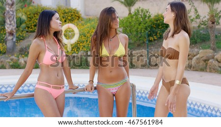 Three sexy shapely girlfriends standing chatting