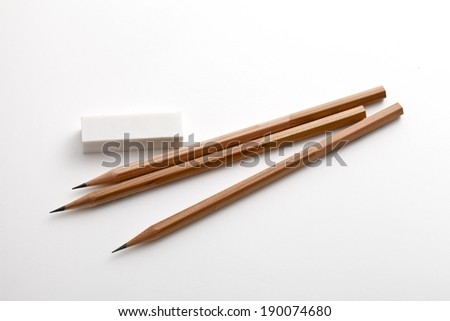Three sharpened pencils and an eraser sitting on a table. - stock photo