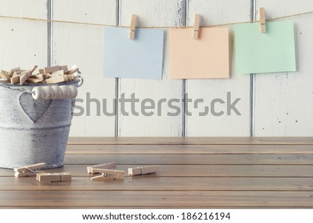 Three sheets of paper hanging on clothespins. A metal bucket with clothespins. Vintage look. - stock photo