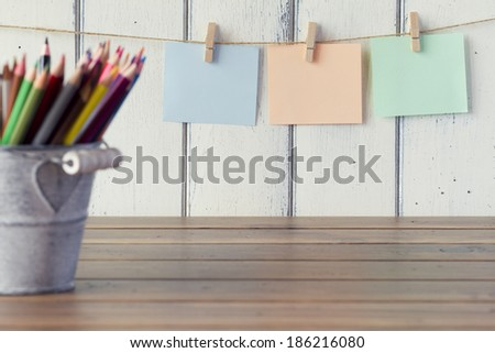 Three sheets of paper hanging on clothespins. Robin egg blue background. A metal bucket with pencils. Vintage look. - stock photo