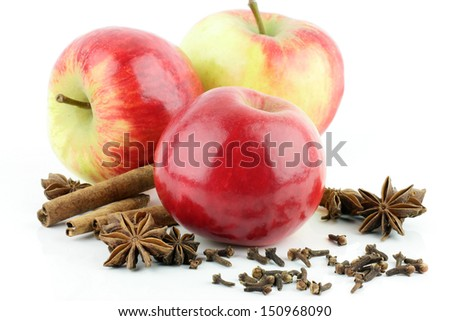 Three shiny fresh red Elstar apple (Malus domestica) with cinnamon, star anise and cloves, on a white background. - stock photo
