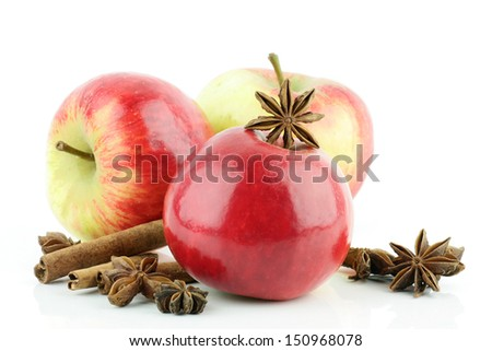 Three shiny fresh red Elstar apples (Malus domestica) with cinnamon and star anise, on a white background. - stock photo