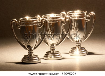 Three shiny trophies standing in a row. - stock photo