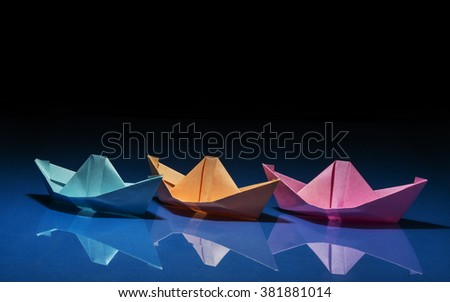 three ships of different colored paper on blue and black background - stock photo