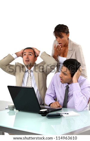 Three shocked business people looking at results - stock photo