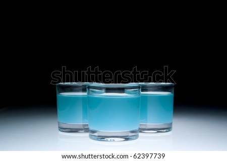 Three shot glasses filled with colored alcohol, black background. - stock photo