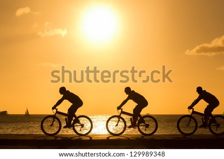 three shot of the man ride bicycles outdoors against sunset. Silhouette.