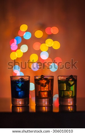 Three shots glasses full of assorted beverages and ice on golden blurred lighting bokeh background. - stock photo