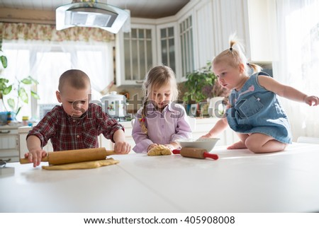 three siblings children preparing cookies in the kitchen,  large family. casual lifestyle photo series in real life interior - stock photo