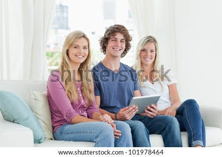Three siblings sit together on the couch as the brother holds the tablet pc while they look at the camera