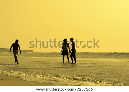 three silhouettes in a beach sunset - stock photo