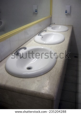 three sinks in a public toilet  - stock photo